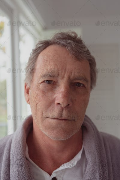 Portrait of active senior Caucasian man looking at camera in a comfortable home