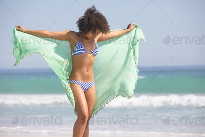 Front view of African american woman in bikini with scarf standing on the beach