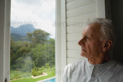 Front view of thoughtful active senior Caucasian man looking through window in a comfortable home