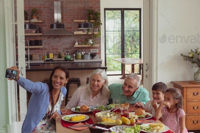 Multi-generation Caucasian family taking selfie with mobile phone while having food on dining table