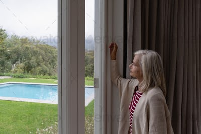 Side view of active senior Caucasian woman looking through window in a comfortable home