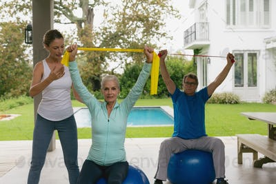 Caucasian female trainer assisting active senior couple to exercise with resistance band