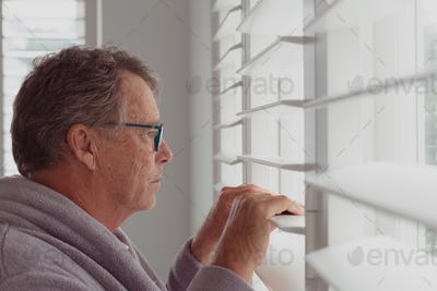 Side view of active senior Caucasian man looking through window in a comfortable home