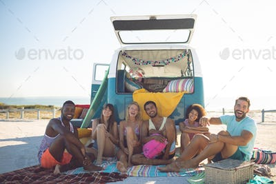 Happy group of diverse friends looking at camera while sitting near camper van at beach