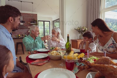 Multi-generation Caucasian family toasting glasses of champagne on dining table at home