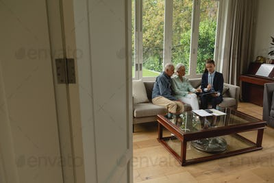 Active senior Caucasian couple discussing with real estate agent over documents in living room
