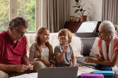 Caucasian grandparents helping grandchildren with homework in living room at comfortable home