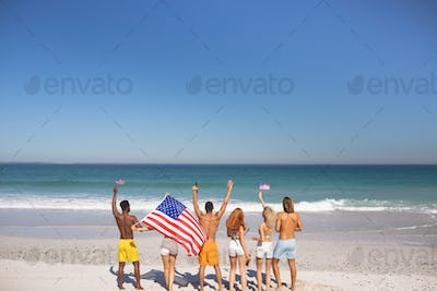 Rear view of a diverse friends raising their hands on the beach while holding american flag