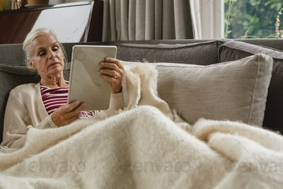 Active senior Caucasian woman relaxing on sofa and using digital tablet in living room
