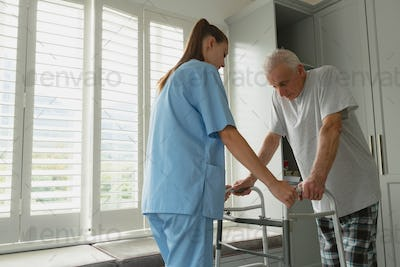 Side view of Caucasian female doctor helping active senior man to walk with walker at home