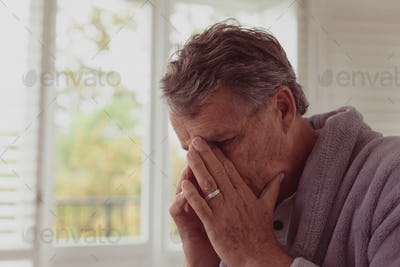 Front view of sad active senior Caucasian man with hands on face in a comfortable home