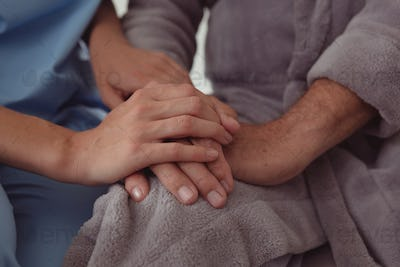Close-up of Caucasian female doctor consoling active senior man in a comfortable home
