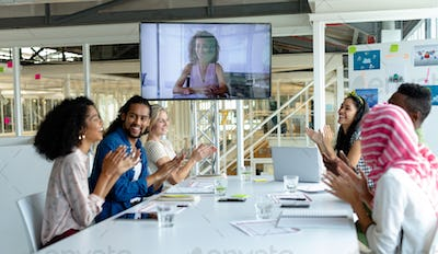 Happy diverse business people applauding during video conference at conference room
