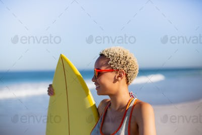 Side view of beautiful African american woman standing with surfboard at beach in the sunshine