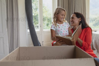 Front view of Caucasian mother and daughter reading a story book in living room at home