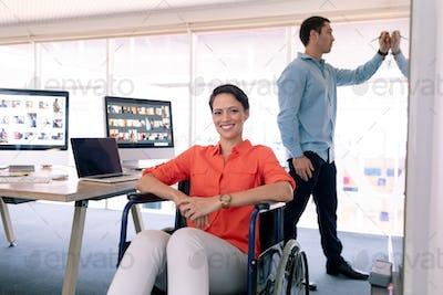 Disabled Caucasian female graphic designer looking at camera