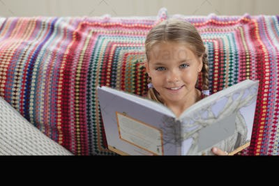 Cute Caucasian girl looking at camera while reading a book on sofa in a comfortable home