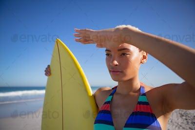 Beautiful African american woman in bikini with surfboard shielding eyes on beach in the sunshine