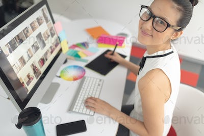 High angle view of Asian female graphic designer using graphic tablet at desk in a modern office
