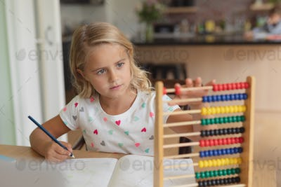 Front view of Caucasian girl doing homework at table in a comfortable home