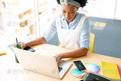 African american female graphic designer using graphic tablet and laptop at desk in office