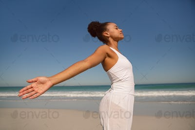 Beautiful African american woman with arms stretched out standing on beach in the sunshine