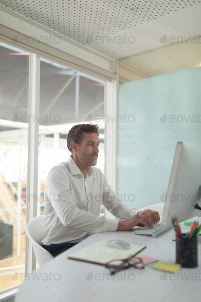 Side view of Caucasian business male executive working on computer at desk in a modern office