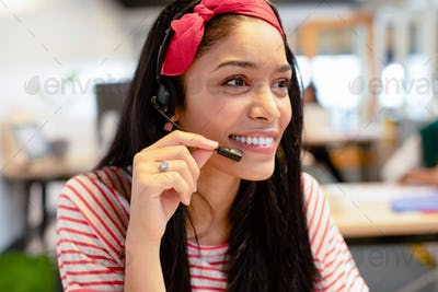 Happy Mixed-race female customer service executive looking at camera while talking on headset