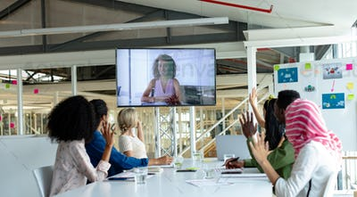 Diverse business people raising hand during video conference at conference room in a modern office