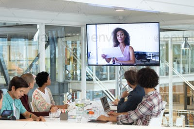 Diverse business people attending video conference at conference room in a modern office