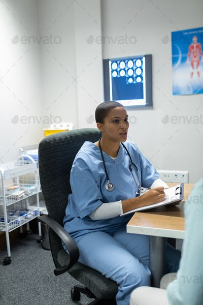 Front view of mixed-race female doctor giving prescription to pregnant woman at desk in hospital