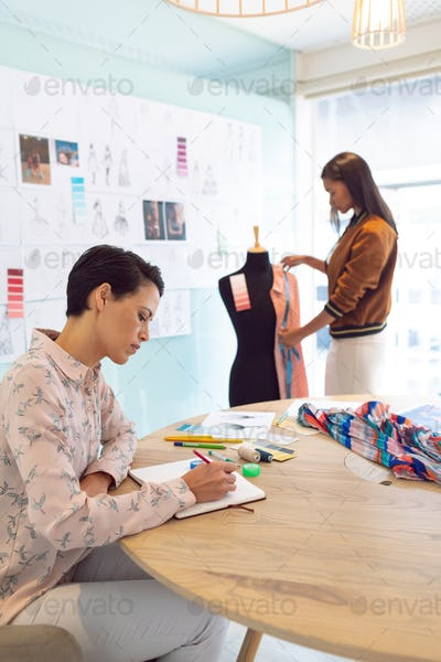 Attentive mixed race female fashion designers working in a modern office.
