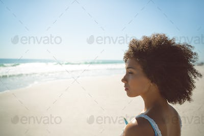 Side view of thoughtful African american woman standing on the beach