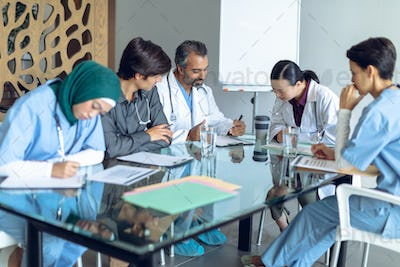 Diverse medical team working together at table in hospital.