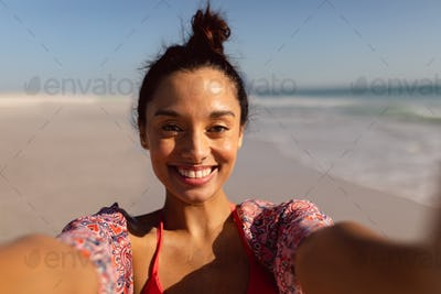 Portrait of young Mixed-race woman in bikini standing on the beach