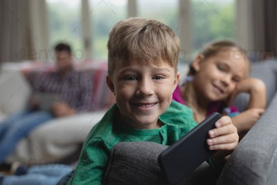 Happy cute Caucasian  boy with mobile phone looking at camera on sofa in a comfortable home