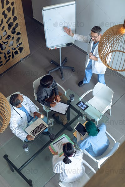 Caucasian male doctor explaining graph on flip chart in meeting with diverse medical team