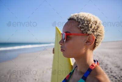 Beautiful African american woman in bikini and sunglasses standing with surfboard
