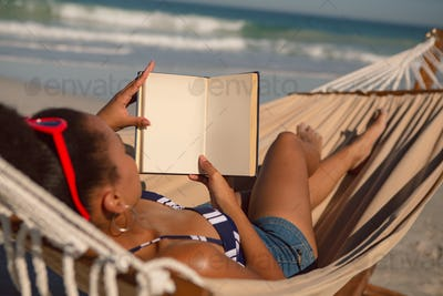 African american woman reading a book while relaxing on hammock on beach in the sunshine