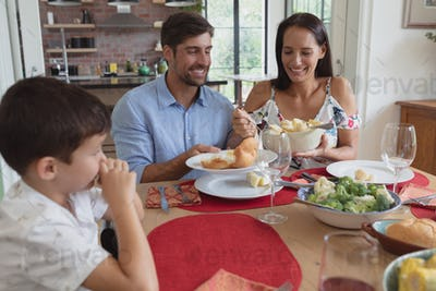 Front view of happy Caucasian family having food at dinning table in a comfortable home