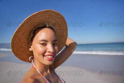 Happy African american woman in bikini and hat looking at camera on beach in the sunshine