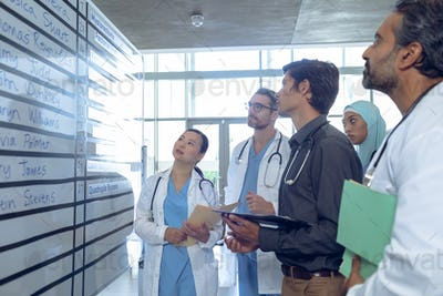 Side view of diverse medical team of doctors checking their shifts on chart at hospital