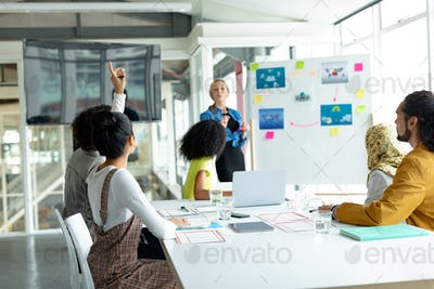 Mixed-raced businesswoman raising hand in presentation during meeting in a modern office