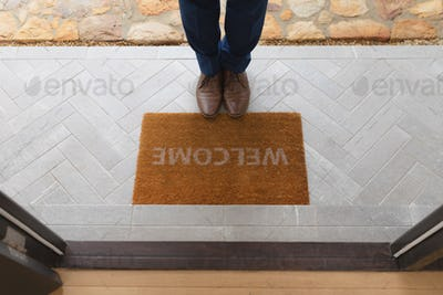 Low section of man standing near welcome mat in front of door at home