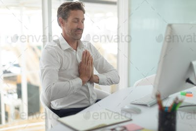 Front view of Caucasian business male executive doing yoga at desk in a modern office