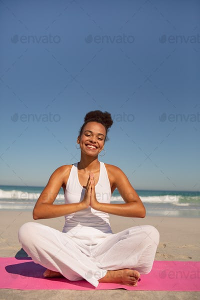 Beautiful happy African american woman doing yoga on exercise mat