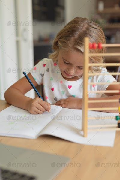 Front view of adorable Caucasian girl study at table in comfortable home