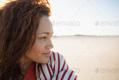 Side view of beautiful mixed race woman wrapped in blanket standing on beach in the sunshine