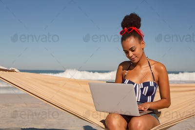 Front view of beautiful African american woman using laptop on hammock at beach in the sunshine