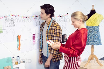 Side view of happy Caucasian male and female fashion designer discussing over sketch in office